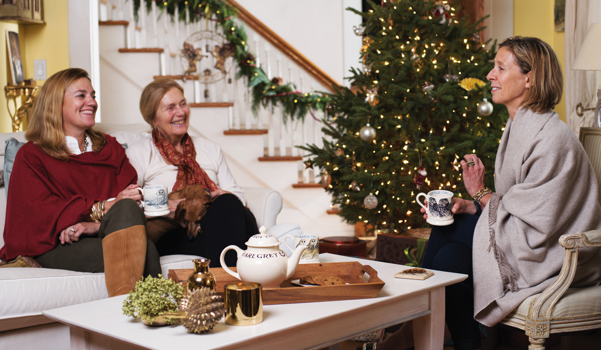 3 women sitting in living room next to Christmas treen drinking tea.